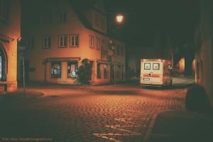 Ein Krankenwagen fährt durch eine nächtliche, menschenleere Straße. Weihnachten arbeiten nur sehr wenige Menschen.